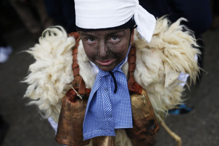"A young boy dressed in sheepskin with jingling bells to make noise, and so called ""Zamarraco"" poses for a photograph during the Vijanera Festival, in the small village of Silio, northern Spain, Sunday, Jan. 3, 2016. The Vijanera masquerade, of pre-Roman origin, is the first carnival of the year in Europe symbolizing the triumph of good over evil and involving the participation of crowds of residents wearing different masks, animal skins and brightly coloured clothing with its own complex function and symbolism and becoming the living example of the survival of archaic cults to nature. (AP Photo/Francisco Seco)"