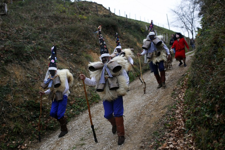 "Men dressed in sheepskins and jingling bells to make noise, and so called ""Zamarracos,"" march during the Vijanera Festival, in the small village of Silio, northern Spain, Sunday, Jan. 3, 2016. The Vijanera masquerade, of pre-Roman origin, is the first carnival of the year in Europe symbolizing the triumph of good over evil and involving the participation of crowds of residents wearing different masks, animal skins and brightly coloured clothing with its own complex function and symbolism and becoming the living example of the survival of archaic cults to nature. (AP Photo/Francisco Seco)"