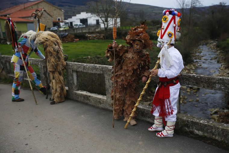People dressed in costumes have a break while marching during the Vijanera Festival, in the small village of Silio, northern Spain, Sunday, Jan. 3, 2016. The Vijanera masquerade, of pre-Roman origin, is the first carnival of the year in Europe symbolizing the triumph of good over evil and involving the participation of crowds of residents wearing different masks, animal skins and brightly coloured clothing with its own complex function and symbolism and becoming the living example of the survival of archaic cults to nature. (AP Photo/Francisco Seco)
