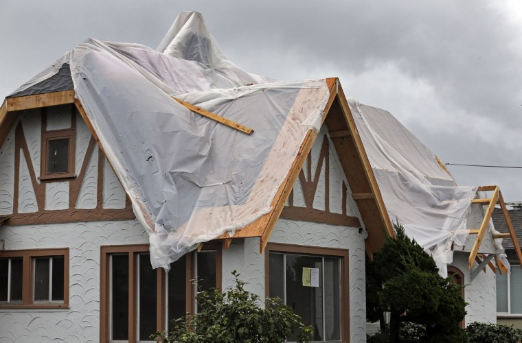 Plastic covers the roof of a home to shield it from rain during a winter storm Tuesday, Jan 5, 2016, in San Leandro, Calif. El Nino storms lined up in the Pacific, promising to drench parts of the West for more than two weeks and increasing fears of mudslides and flash floods in regions stripped bare by wildfires. At least two more storms are expected to follow on Wednesday and Thursday, bringing as much as 3 inches of rain. (AP Photo/Ben Margot)