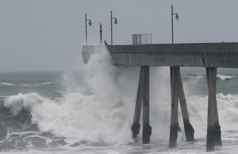 A man stands near crashing waves on the Pacifica Pier in Pacifica, Calif., Tuesday, Jan. 5, 2016. El Nino storms lined up in the Pacific, promising to drench parts of the West for more than two weeks and increasing fears of mudslides and flash floods in regions stripped bare by wildfires. (AP Photo/Jeff Chiu)