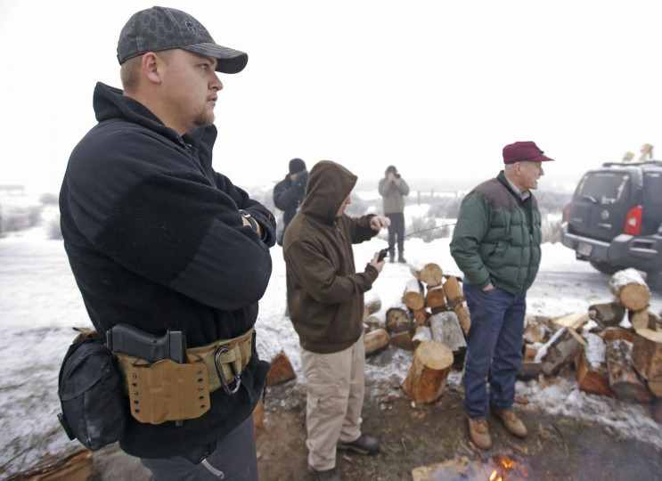 """A member of the group occupying the Malheur National Wildlife Refuge headquarters looks on Thursday, Jan. 7, 2016, near Burns, Ore. Cheers erupted Wednesday evening at a packed community meeting in rural Oregon when a sheriff said it was time for a small, armed group occupying the national wildlife refuge to """"pick up and go home."""" (AP Photo/Rick Bowmer)"""