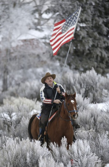 Cowboy Dwane Ehmer, of Irrigon Ore., a supporter of the group occupying the Malheur National Wildlife Refuge, holds a U.S. flag as he rides his horse in the refuge Thursday, Jan. 7, 2016, near Burns, Ore. A small, armed group occupying the wildlife preserve has said repeatedly that local people should control federal lands, but critics say the lands are already managed to help everyone from ranchers to recreationalists. (AP Photo/Rick Bowmer)