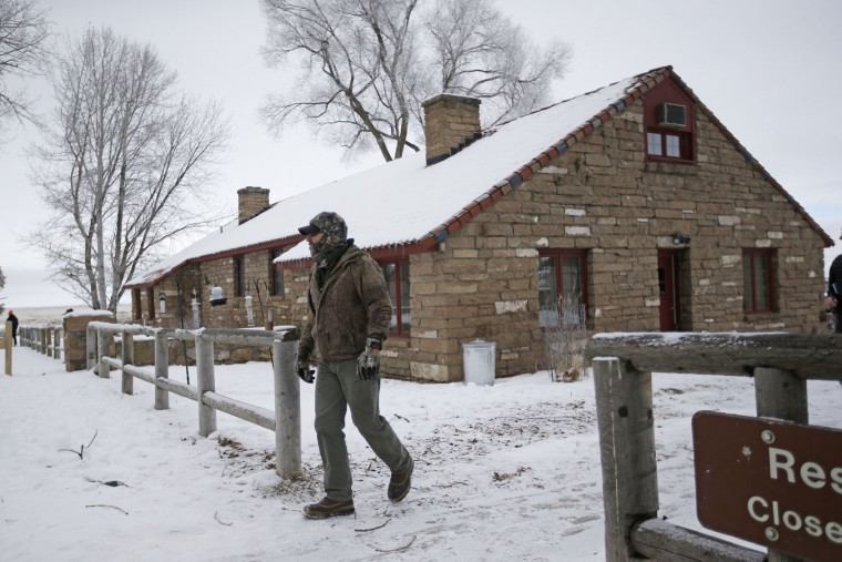 "A member of the group occupying the Malheur National Wildlife Refuge, walks from one of it's buildings Thursday, Jan. 7, 2016, near Burns, Ore. Cheers erupted at a packed community meeting in rural Oregon when a sheriff said it was time for a small, armed group occupying a national wildlife refuge to ""pick up and go home."" (AP Photo/Rick Bowmer)"