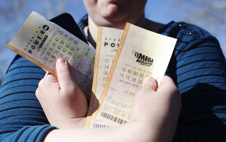 "Stephanie Barnett, of Center Point, Ala., holds up Powerball lottery tickets at Georgia Visitor Information Center, Wednesday, Jan. 13, 2016, in Tallapoosa, Ga. ""If I win, I want to build a new house,"" says Barnett. (AP Photo/Brynn Anderson)"