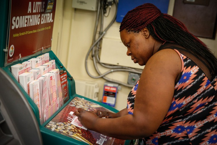 Tameka McGriff fills her numbers a she gets set to purchase Powerball lottery tickets at a Chevron Station in Tampa, Fla., on Wednesday, Jan. 13, 2016. The Powerball jackpot for Wednesday night's drawing is at least $1.5 billion, the largest lottery jackpot in the world. (Loren Elliott/The Tampa Bay Times via AP)
