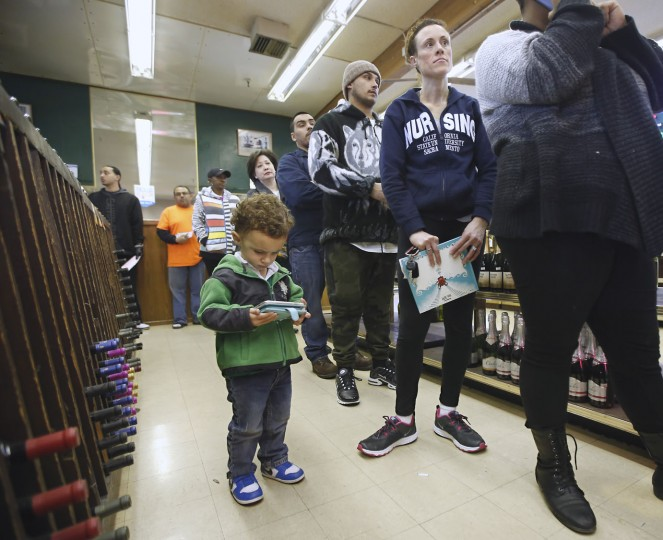 Rose Castro, right, waits to purchase Powerball Lottery tickets as her son, Roman, 1, plays with her mobile device at Lichine's Liquor store, Wednesday, Jan. 13, 2016, in Sacramento, Calif. The Powerball jackpot for Wednesday night's drawing is estimated to be over $1 billion, the largest lottery jackpot in the world.(AP Photo/Rich Pedroncelli)