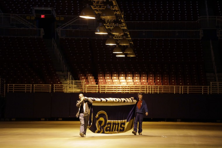 Jack Dungy, right, and Jim McNeely, decorators with Local 39, carry away the 1999 Super Bowl championship banner after it was removed from the ceiling of the Edward Jones Dome, former home of the St. Louis Rams football team, Thursday, Jan. 14, 2016, in St. Louis. The Rams will begin playing in Los Angeles starting with the 2016 season. (AP Photo/Jeff Roberson)