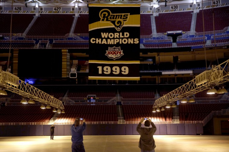 Jack Dungy and Jim McNeely, right, decorators with Local 39, take pictures as the Super Bowl XXXIV championship banner is removed from the ceiling of the Edward Jones Dome, former home of the St. Louis Rams football team, Thursday, Jan. 14, 2016, in St. Louis. The Rams will begin playing in Los Angeles starting with the 2016 season. (AP Photo/Jeff Roberson)