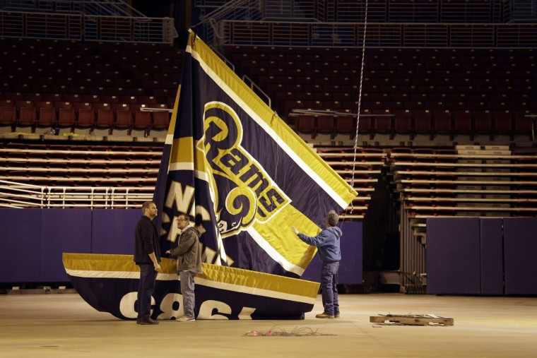 Championship banners are removed from the ceiling of the Edward Jones Dome, former home of the St. Louis Rams football team, Thursday, Jan. 14, 2016, in St. Louis. The Rams will begin playing in Los Angeles starting with the 2016 season. (AP Photo/Jeff Roberson)