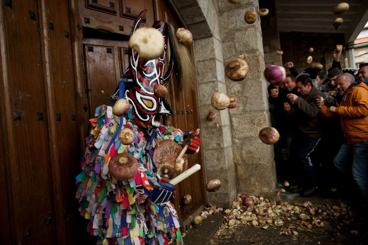 People throw turnips at the Jarramplas as he comes out from the church beating his drum during the Jarramplas Festival on January 20, 2016 in Piornal, Caceres province, Spain. The centuries old Jarramplas festival takes place annually every January 19-20 on Saint Sebastian Day and this year they expect to use more than 20 thousand kilogrames of turnips. Even though the exact origins of the festival are not known, various theories exist including the mythological punishment of Caco by Hercules, a relation to ceremonies celebrated by the American Indians that were seen by the first conquerors, to a cattle thief ridiculed and expelled by his village neighbours. It is generally believed to symbolize the expulsion of everything bad. (Pablo Blazquez Dominguez/Getty Images)