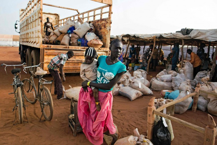 "An asylum seeker and her baby from Sudan, who recently arrived in South Sudan, stands beside a truck holding some of her belongings before she is transferred to the refugee camp in Ajuong Thok, near Yida, northern South Sudan, on January 26, 2016. Both South Sudan's Rebel leader Riek Machar and South Sudan's President Salva Kiir signed a peace deal in August but have consistently broken ceasefires. The opposing sides missed a January 22, 2016 deadline to form a unity government amid a dispute over Kiirs reorganization of the oil-producing country into 28 states. United Nations (UN) sanctions monitors have stated in a confidential report that The U.N Security Council should place an arms embargo on South Sudan, and that both President Kiir and Riek Machar ""qualify"" for sanctions over atrocities committed during the two year civil war in the country. The civil war in South Sudan has left tens of thousands of people dead and forced more than 2 million others to flee their homes since erupting in December 2013. (Albert Gonzalez Ferran/AFP/Getty Images)"