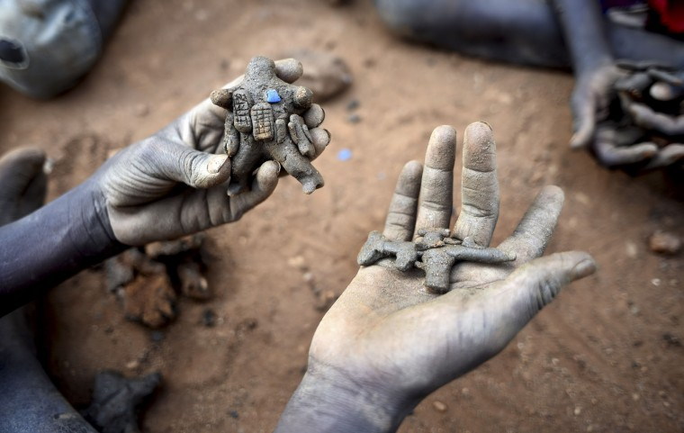 In this photo taken Tuesday, Jan. 19, 2016, a displaced child holds clay model toys of a peacekeeper and a rifle, in the United Nations camp for displaced people in the capital Juba, South Sudan. When a delegation of South Sudanese rebels returned to the government-controlled capital Juba last month after two years of war, many refugees thought they would finally return to the homes they fled. But prospects for peace seem dim after the government and rebels missed a deadline last week to form a power-sharing government and end the war. President Salva Kiir, an ethnic Dinka, and rebel leader Riek Machar, a Nuer, signed a peace deal in August, but fighting continues. Machar said Tuesday, Jan. 26 in Kampala, Uganda that he won't return to Juba, South Sudan's capital, because the decree violated the peace accord. (AP Photo/Jason Patinkin)