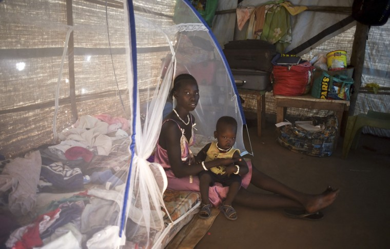 In this photo taken Tuesday, Jan. 19, 2016, Nyajok Koat sits with her one year-old son Thach Kuony in her makeshift home covered with plastic sheets, in the United Nations camp for displaced people in the capital Juba, South Sudan. When a delegation of South Sudanese rebels returned to the government-controlled capital Juba last month after two years of war, many refugees thought they would finally return to the homes they fled. But prospects for peace seem dim after the government and rebels missed a deadline last week to form a power-sharing government and end the war. President Salva Kiir, an ethnic Dinka, and rebel leader Riek Machar, a Nuer, signed a peace deal in August, but fighting continues. Machar said Tuesday, Jan. 26 in Kampala, Uganda that he won't return to Juba, South Sudan's capital, because the decree violated the peace accord. (AP Photo/Jason Patinkin)