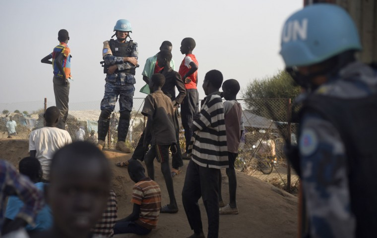 In this photo taken Tuesday, Jan. 19, 2016, a United Nations peacekeeper stands with displaced children on a wall around the United Nations base in the capital Juba, South Sudan. When a delegation of South Sudanese rebels returned to the government-controlled capital Juba last month after two years of war, many refugees thought they would finally return to the homes they fled. But prospects for peace seem dim after the government and rebels missed a deadline last week to form a power-sharing government and end the war. President Salva Kiir, an ethnic Dinka, and rebel leader Riek Machar, a Nuer, signed a peace deal in August, but fighting continues. Machar said Tuesday, Jan. 26 in Kampala, Uganda that he won't return to Juba, South Sudan's capital, because the decree violated the peace accord. (AP Photo/Jason Patinkin)