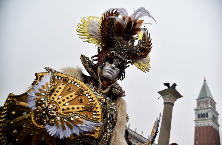 "A costumed reveller poses at St Mark's square (Piazza San Marco) during the Venice Carnival in Venice on January 30, 2016. The 2016 edition of the Venice carnival is entitled ""Creatum"" and runs until February 9th. (Vincenzo Pinto/AFP/Getty Images)"