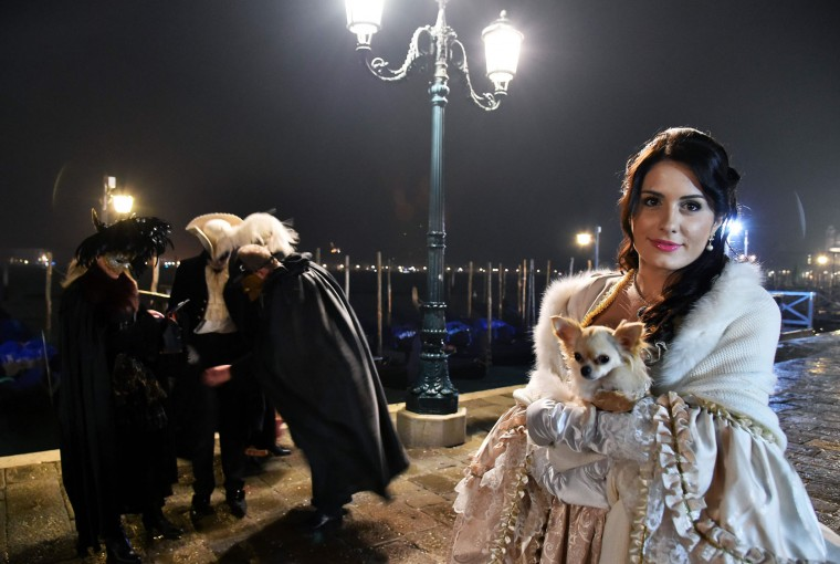 "A costumed reveller poses in front of gondolas at St Mark's square (Piazza San Marco) during the Venice Carnival on January 30, 2016 in Venice. The 2016 edition of the Venice carnival is untitled "" Creatum "" and runs until February 9th. (Vincenzo Pinto/AFP/Getty Images)"