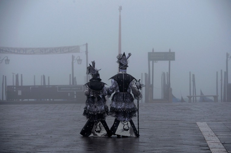 "Revellers in costumes arrive to attend the performance of the ""Angel flight"" or ""Flight of the dove"" from the bell tower of Saint Mark's square (Piazza San Marco) to officially launch the Venice Carnival on January 31, 2016. The 2016 edition of the Venice carnival has for theme ""Creatum"" and runs until February 9. (Vincenzo Pinto/AFP/Getty Images)"