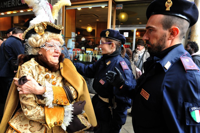 A masked woman goes through a security check in Venice, Italy, Sunday, Jan. 31, 2016. People attended the Venice Carnival, celebrated Saturday under heightened security following the sexual assaults on New Year's Eve in Cologne and the ongoing terror threat in Europe. Authorities have increased surveillance throughout the city, including the number of officers on patrol, both under-cover and in uniform. (AP Photo/Luigi Costantini)