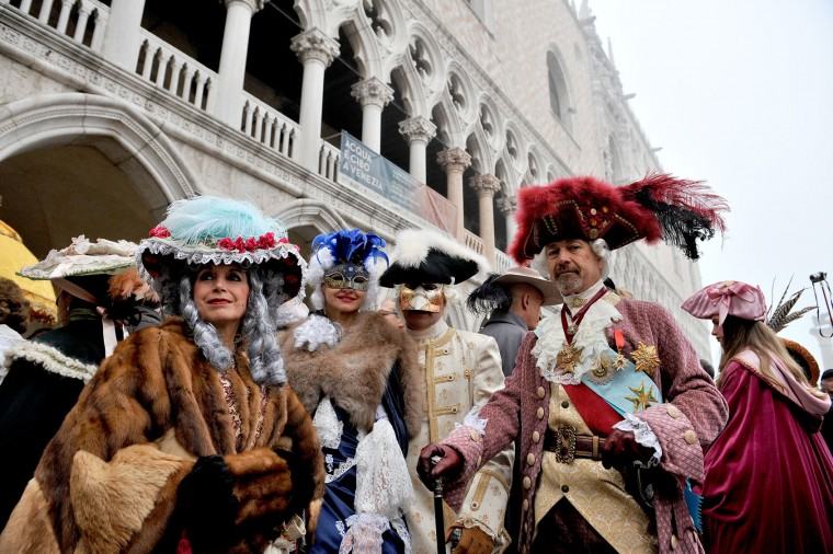 Masked people pose in Venice, Italy, Sunday, Jan. 31, 2016. People attended the Venice Carnival, celebrated Saturday under heightened security following the sexual assaults on New Year's Eve in Cologne and the ongoing terror threat in Europe. Authorities have increased surveillance throughout the city, including the number of officers on patrol, both under-cover and in uniform. (AP Photo/Luigi Costantini)