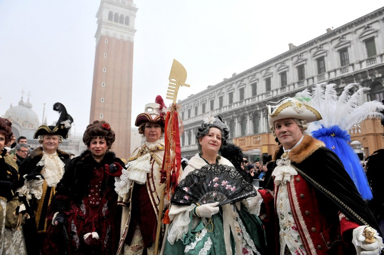People wearing costumes pose in St. Mark's Square in Venice, Italy, Sunday, Jan. 31, 2016. Carnival-goers in Venice are being asked by police to momentarily lift their masks as part of new anti-terrorism measures for the annual festivities. Police are also examining backpacks and bags and using metal-detecting wands before revelers are allowed into St. Mark's Square, the heart of the Venetian carnival. (AP Photo/Luigi Costantini)
