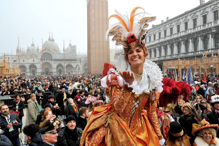 "Irene Rizzi blows a kiss after descending from the bell tower into St. Mark's Square, in Venice, Sunday, Jan. 31, 2016. Carnival-goers in Venice are being asked by police to momentarily lift their masks as part of new anti-terrorism measures for the annual festivities. Sunday's main crowd-pleaser known as the Flight of the Angel went off without a hitch. In that event, a costumed young woman, attached by wires, "" flies "" over the crowd, starting from St. Mark's bell tower and gradually descending to the square. (AP Photo/Luigi Costantini)"