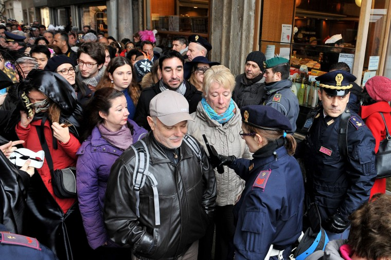 People go through security checks in St. Mark's Square, in Venice, Sunday, Jan. 31, 2016. Carnival-goers in Venice are being asked by police to momentarily lift their masks as part of new anti-terrorism measures for the annual festivities. Police are also examining backpacks and bags and using metal-detecting wands before revelers are allowed into St. Mark's Square, the heart of the Venetian carnival. (AP Photo/Luigi Costantini)