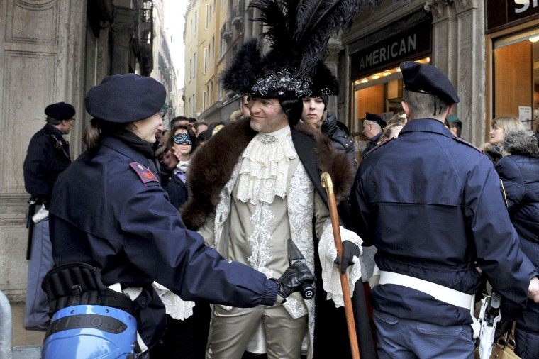 A police officer checks a man wearing a carnival costume in Venice, Italy, Sunday, Jan. 31, 2016. Carnival-goers in Venice are being asked by police to momentarily lift their masks as part of new anti-terrorism measures for the annual festivities. Police are also examining backpacks and bags and using metal-detecting wands before revelers are allowed into St. Mark's Square, the heart of the Venetian carnival.(AP Photo/Luigi Costantini)