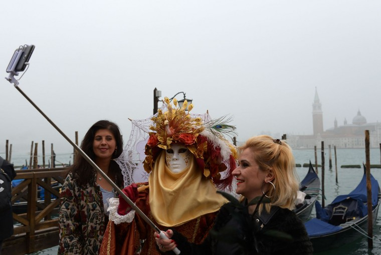 "Costumed reveller poses for selfie in St Mark's square (Piazza San Marco) after the officially launch of the Venice Carnival on January 31, 2016 in Venice. The 2016 edition of the Venice carnival is untitled ""Creatum"" and runs until February 9th. (Vincenzo Pinto/AFP/Getty Images)"