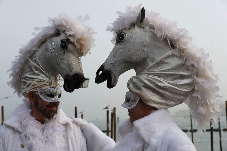 "Costumed revellers pose in St Mark's square (Piazza San Marco) after the officially launch of the Venice Carnival on January 31, 2016 in Venice. The 2016 edition of the Venice carnival is untitled ""Creatum "" and runs until February 9th. (Vincenzo Pinto/AFP/Getty Images)"