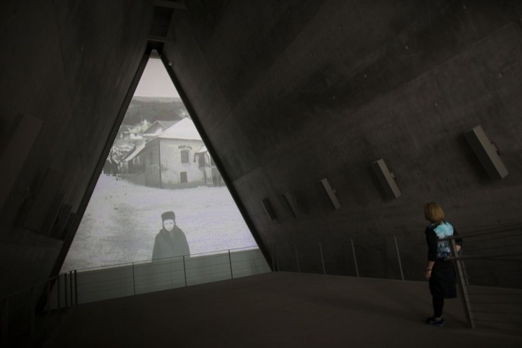A woman watches a film as it is screened at the Yad Vashem Holocaust museum, which commemorates the six million Jews killed by the Nazis during World War II on January 27, 2014 in Jerusalem, Israel. The international Holocaust Remembrance Day is marked today around the globe. (Photo by Uriel Sinai/Getty Images)