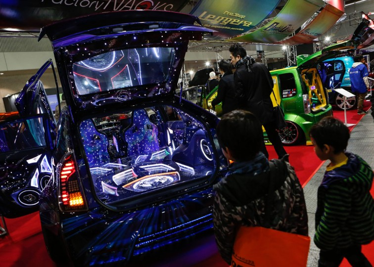 Two boys look at the custom audio system inside the interior of a car shown on display at the 2016 Tokyo Auto Salon car show on January 15, 2016 in Chiba, Japan. (Photo by Christopher Jue/Getty Images)