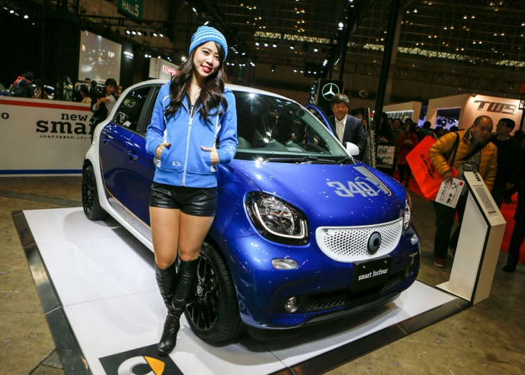 A campaign model poses next to a Mercedes-Benz smart forfour passion vehicle on display at the 2016 Tokyo Auto Salon car show on January 15, 2016 in Chiba, Japan. TOKYO AUTO SALON 2016 is held from January 15 to 17, 2016. (Photo by Christopher Jue/Getty Images)