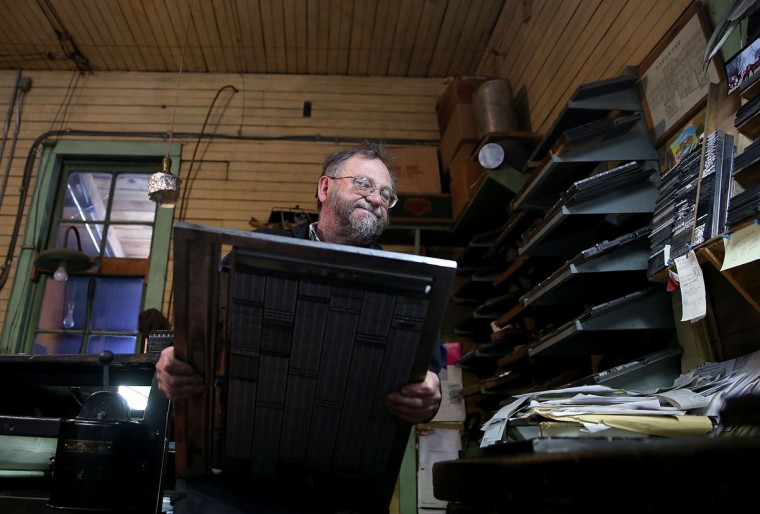 Saguache Crescent owner and editor Dean Coombs carries a plate of metal type text before printing the Saguache Crescent newspaper on January 19, 2016 in Saguache, Colorado. The Saguache Crescent newspaper is the last newspaper in the United States that is produced using a Linotype hot metal typesetting machine. Dean Coombs, the paper's owner and editor, has been publishing the small town newspaper once a week using a Linotype machine that was purchased new in 1921, a few years after his family took over the paper in 1917. Coombs has been running the business by himself for the past 38 years and has no plans of shutting its doors anytime soon. Most newspapers discontinued the use of Linotypes over 40 years ago and were replaced with offset lithography printing and computer typesetting. (Photo by Justin Sullivan/Getty Images)