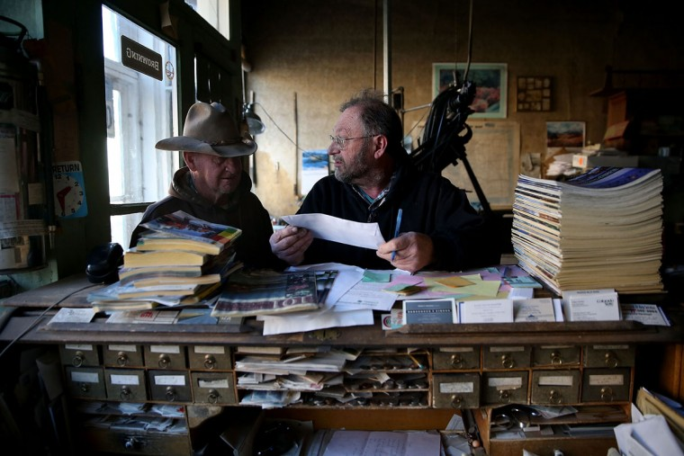 Saguache Crescent owner and editor Dean Coombs (R) helps a customer with rubber stamp order at the Saguache Crescent newspaper on January 19, 2016 in Saguache, Colorado. The Saguache Crescent newspaper is the last newspaper in the United States that is produced using a Linotype hot metal typesetting machine. Dean Coombs, the paper's owner and editor, has been publishing the small town newspaper once a week using a Linotype machine that was purchased new in 1921, a few years after his family took over the paper in 1917. Coombs has been running the business by himself for the past 38 years and has no plans of shutting its doors anytime soon. Most newspapers discontinued the use of Linotypes over 40 years ago and were replaced with offset lithography printing and computer typesetting. (Photo by Justin Sullivan/Getty Images)