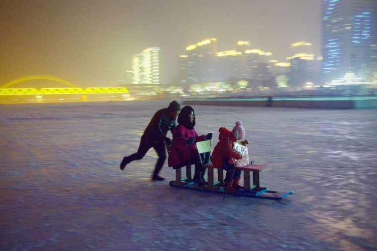A family drive a sleigh on frozen Songhua river beside the Harbin international ice and snow festival in Harbin, northeast China's Heilongjiang province on January 3, 2016. (WANG ZHAO/AFP/Getty Images)