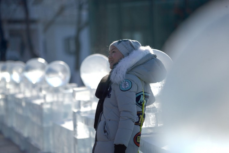 A woman poses for a picture in front of ice sculptures before the opening ceremony of the Harbin International Ice and Snow Festival in Harbin, northeast China's Heilongjiang province on January 4, 2016. (WANG ZHAO/AFP/Getty Images)