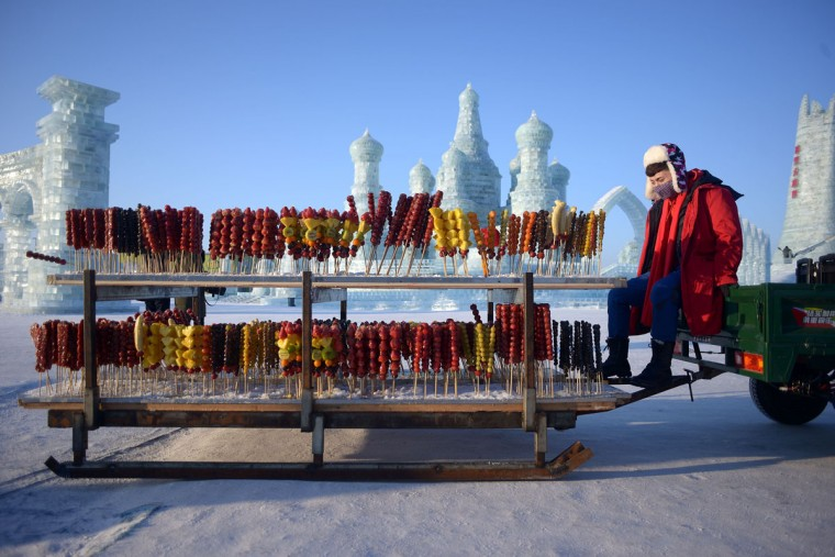 A vendor selling candied haws waits for customers at the China Ice and Snow World before the opening ceremony of the Harbin International Ice and Snow Festival in Harbin, northeast China's Heilongjiang province on January 4, 2016. (WANG ZHAO/AFP/Getty Images)