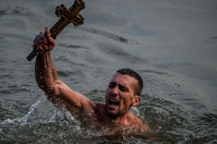 Greek Orthodox swimmer Nicolaos Solis holds a wooden cross retrieved from the Bosphorus river's Golden Horn, as part of celebrations of the Epiphany day at the Church of Fener Orthodox Patriarchate in Istanbul, on January 6, 2016. Similar celebrations for the Epiphany Day are held across the country and region on river banks, seafronts and lakes. The Orthodox faith uses the old Julian calendar in which Christmas falls 13 days after its more widespread Gregorian calendar counterpart that celebrates Christmas on December 25. (AFP Photo / Ozan Kose)
