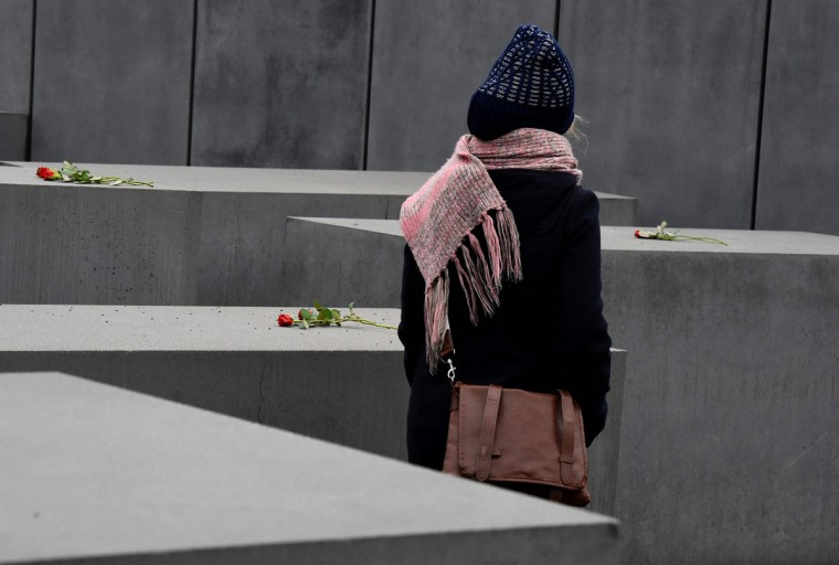 A woman look at flowers placed on the concrete columns of the Holocaust memorial during the international Holocaust Remembrance Day in Berlin on January 27, 2016. (AFP Photo / Tobias Schwarz)