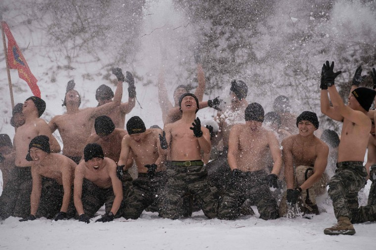 South Korean and US soldiers hurl snow into the air as they pose for photographers during a joint annual winter exercise in Pyeongchang, some 180 kilometers east of Seoul, on January 28, 2016. The Korean peninsula is the world's last Cold War frontier as Stalinist North Korea and pro-Western South Korea have been technically at war since the 1950-53 conflict. (ED JONES/AFP/Getty Images)