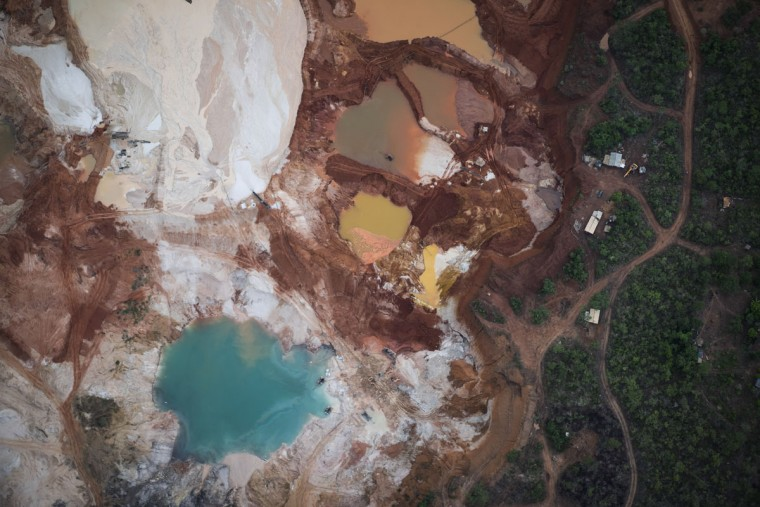 This Nov. 18, 2015 photo shows an area that was destroyed by diamond mining at an abandoned mine in Areinha, Minas Gerais state, Brazil. The devastated area known as Areinha is a no manís land where small groups of artisanal miners try their luck in the craters left behind by multinational mining companies. (AP Photo/Felipe Dana)