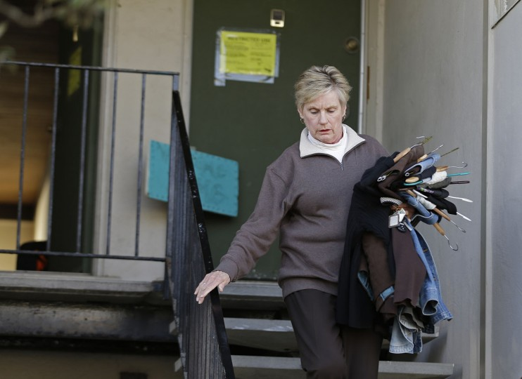 Eileen Horan carries away some of her clothes after being forced to evacuate her apartment Monday, Jan. 25, 2016, in Pacifica, Calif. El Nino storms delivering crashing waves and powerful rain storms have put homes perched atop coastal bluffs near San Francisco in danger, forcing residents of an apartment complex on Monday to leave. (AP Photo/Eric Risberg)