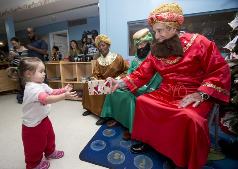 Valerie Martinez, 2, receives a gift from Pablo Torrens, right, who with Bruno Carreras, center rear, and Venicio A. Hernandez, second from right, play the roll of the three wise men during a Three Kings Day toy giveaway sponsored by the Kiwanis Club of Little Havana and the Marlins Foundation, at the Little Havana Activities and Nutrition Center, Wednesday, Jan. 6, 2016, in the Little Havana neighborhood of Miami. The holiday celebrates Epiphany and the arrival of the Three Kings and is the last of the 12 days of Christmas. (AP Photo/Wilfredo Lee)