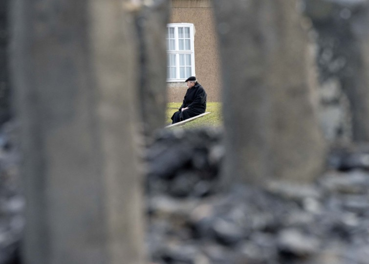 A man sits behind the Holocaust memorial stones during the international Holocaust remembrance day in the former Nazi concentration camp Buchenwald near Weimar, central Germany, Wednesday, Jan. 27, 2016. (AP Photo/Jens Meyer)