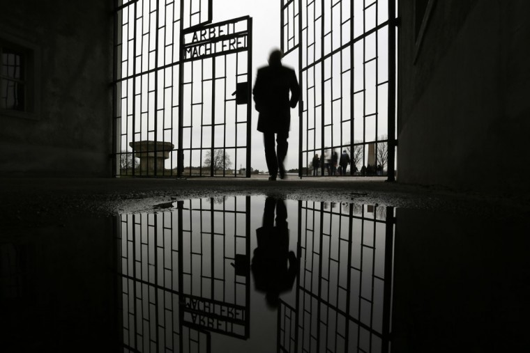A man enters the Sachsenhausen Nazi death camp through the gate with the phrase 'Arbeit macht frei' (work sets you free) at the International Holocaust Remembrance Day, in Oranienburg, about 30 kilometers, (18 miles) north of Berlin, Wednesday, Jan. 27, 2016. The International Holocaust Remembrance Day marks the liberation of the Auschwitz Nazi death camp on Jan. 27, 1945. (AP Photo/Markus Schreiber)