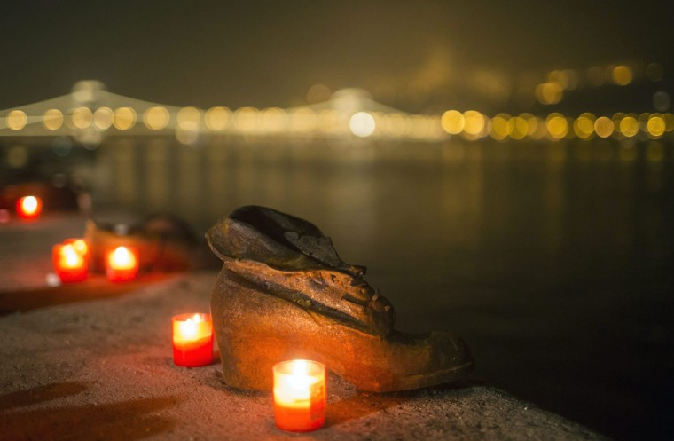 Candles burn in front of the cast iron shoes at the Holocaust Memorial on the quay of the River Danube, during International Holocaust Remembrance Day in Budapest, Hungary, Wednesday, Jan. 27, 2016. International Holocaust Remembrance Day marks the liberation of Auschwitz-Birkenau Nazi concentration camp by Soviet troops on Jan. 27, 1945. (Balazs Mohai/MTI via AP)