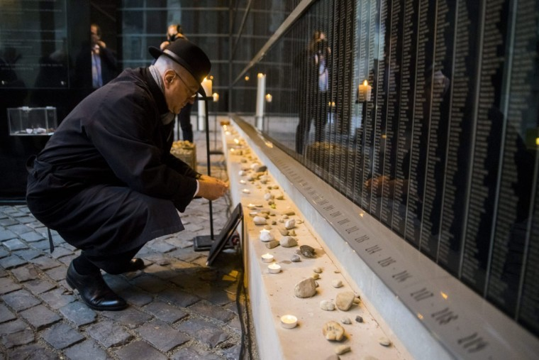 Israeli Ambassador to Hungary Ilan Mor lights a candle at the Victims' Memorial Wall, during a commemoration marking International Holocaust Remembrance Day in the Holocaust Memorial Centre in Budapest, Hungary, Wednesday, Jan. 27, 2016. The remembrance day coincides with the 71st anniversary of the liberation of the Auschwitz Nazi concentration camp. (Zoltan Balogh/MTI via AP)