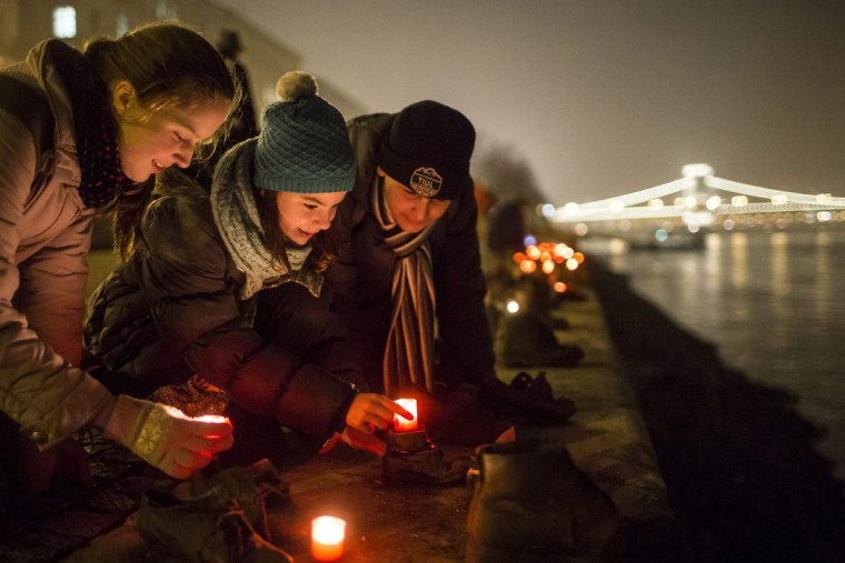 Backdropped by the illuminated Chain Bridge, people light candles in front of the cast iron shoes at the Holocaust Memorial on the quay of the River Danube, during International Holocaust Remembrance Day in Budapest, Hungary, Wednesday, Jan. 27, 2016. International Holocaust Remembrance Day marks the liberation of Auschwitz-Birkenau Nazi concentration camp by Soviet troops on Jan. 27, 1945. (Balazs Mohai/MTI via AP)