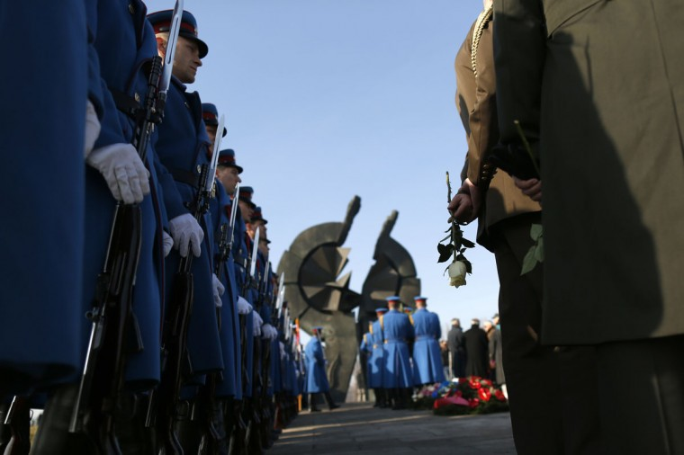A foreign military personnel holds a flower as members of the the military wait in line to pay their respects, at a memorial service to the victims of the Holocaust at a monument in World War II Nazi concentration camp Sajmiste, in Belgrade, Serbia, Wednesday, Jan. 27, 2016. The international Holocaust remembrance day marks the liberation of the Nazi concentration camp Auschwitz on Jan. 27, 1945. (AP Photo/Darko Vojinovic)